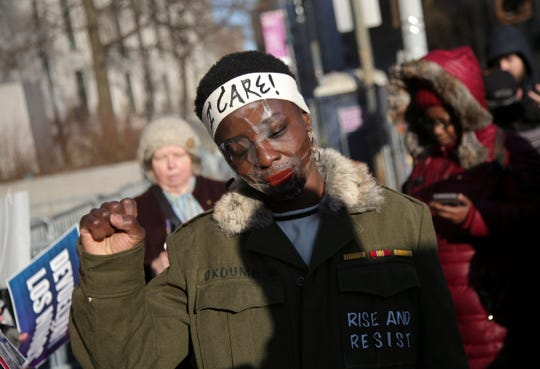 Therese Okoumou poses for pictures and rallies with supporters before her sentencing in New York, Tuesday, March 19, 2019. Okoumou was convicted of trespassing and other offenses after she climbed the base of the Statue of Liberty on July 4, 2018. (AP Photo/Seth Wenig)