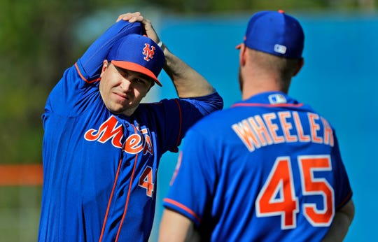 FILE - In this Feb. 14, 2019, file photo, New York Mets pitcher Jacob deGrom, left, talks with teammate Zack Wheeler while stretching during spring training baseball practice in Port St. Lucie, Fla.