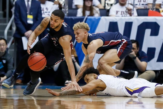 Fairleigh Dickinson's Darnell Edge (left) and Jahlil Jenkins scramble after a loose ball against Prairie View A&M's Dennis Jones, bottom right, during a First Four game of the NCAA men's college basketball tournament, Tuesday, March 19, 2019, in Dayton, Ohio.