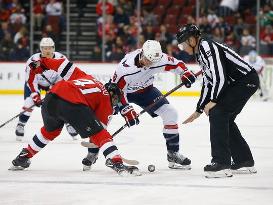 Washington Capitals center Nic Dowd (26) and New Jersey Devils center Michael McLeod (41) battle for the puck in a face off during the first period at Prudential Center.