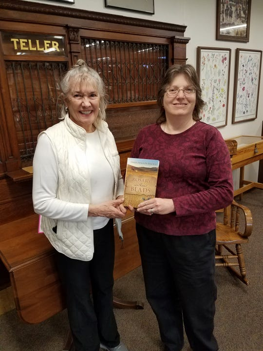 "Author Diana Holguin-Balogh presents a copy of her book ""Rosary without Beads"" to Alamogordo Public Library Manager 	Sharon Rowe."