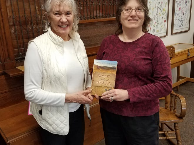 """Author Diana Holguin-Balogh presents a copy of her book """"Rosary without Beads"""" to Alamogordo Public Library Manager Sharon Rowe."""
