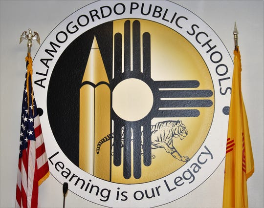 Alamogordo Public Schools logo with flags in APS School Board meeting room.