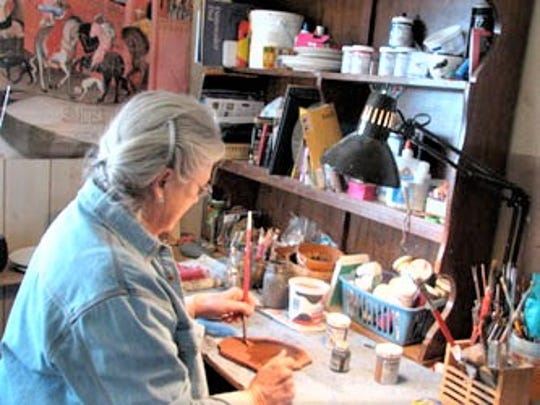 Jeannie Adams is at work in her studio, painting on rock.