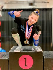 Northville native Sophia Reddy poses after winning the level nine state title on bars.