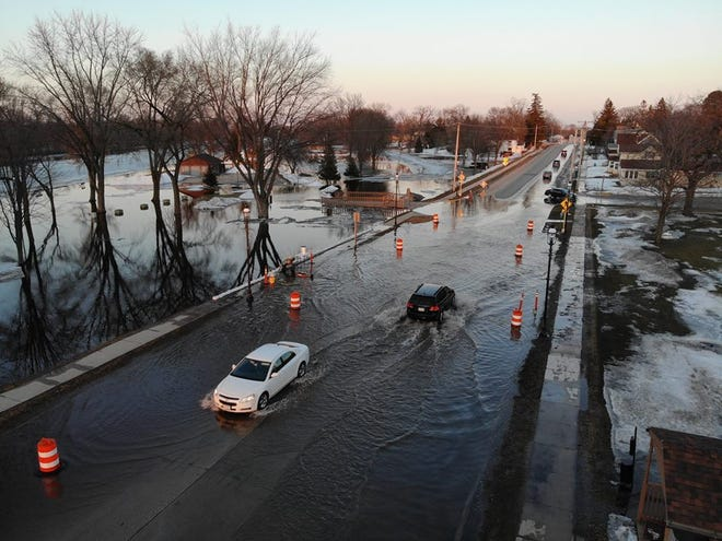 Cars travel over a flooded Omro highway.