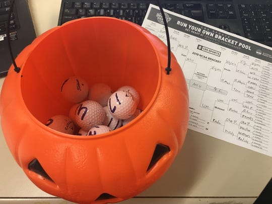The tools for a new system for filling out a bracket. The golf balls say Michigan State will hoist the trophy.