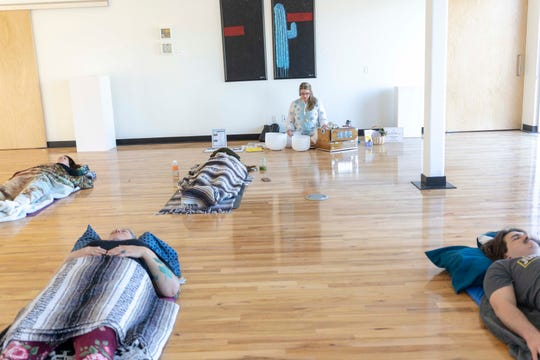 Nicole Anne Fonovich, owner of Nicole Anne Yoga, teaches meditation during a yoga class at the Mesa Artspace Lofts.