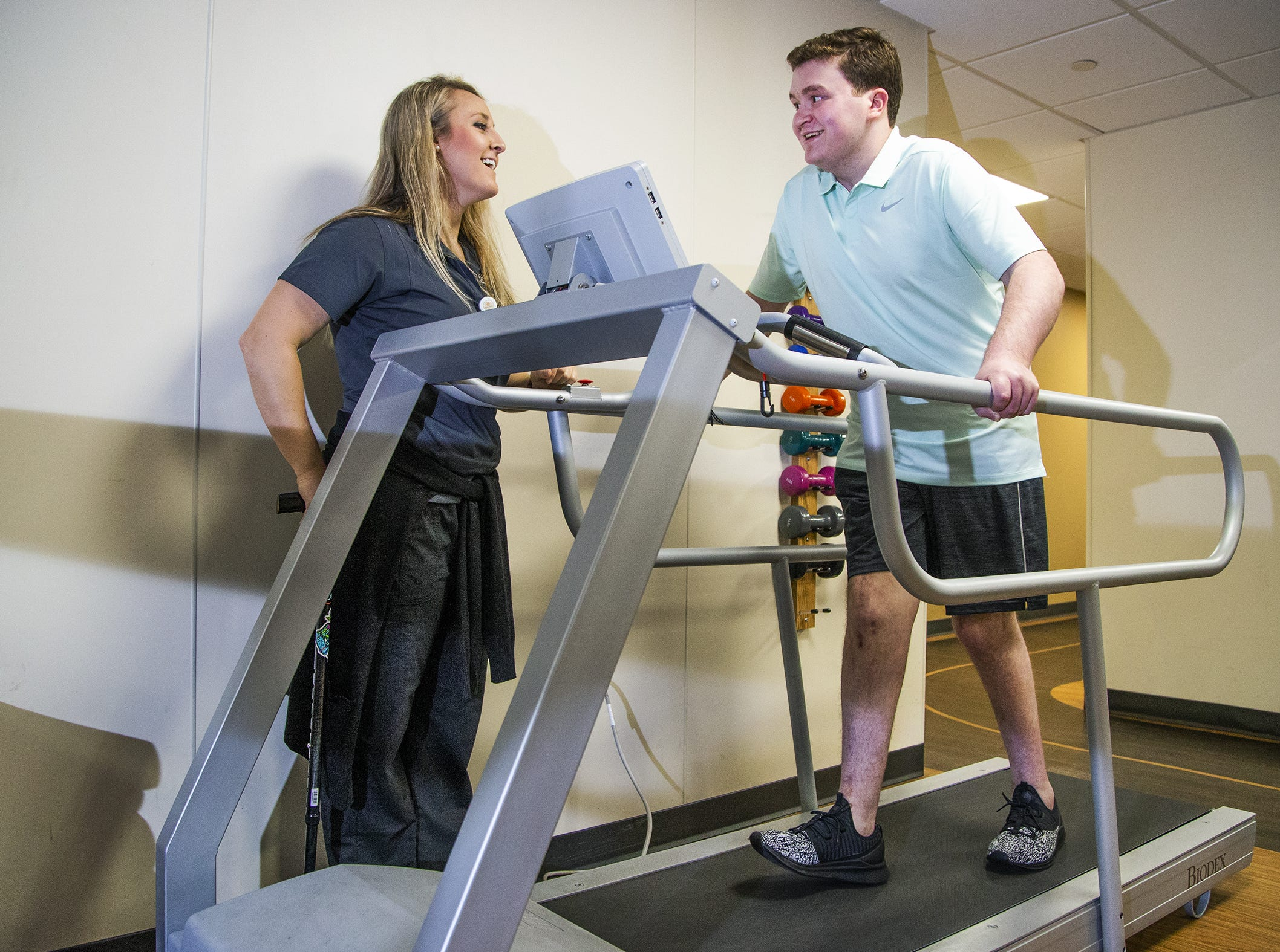 Brody Burnell, 20, right, survived a horrific airplane crash in 2017 and has made a miraculous recovery from multiple injuries, including traumatic brain injury.  He works the treadmill with his physical therapist, Laura Baumert, D.P.T., at the Neuro-Rehabilitation Center at Barrow Neurological Institute, Tuesday, March 19, 2019.