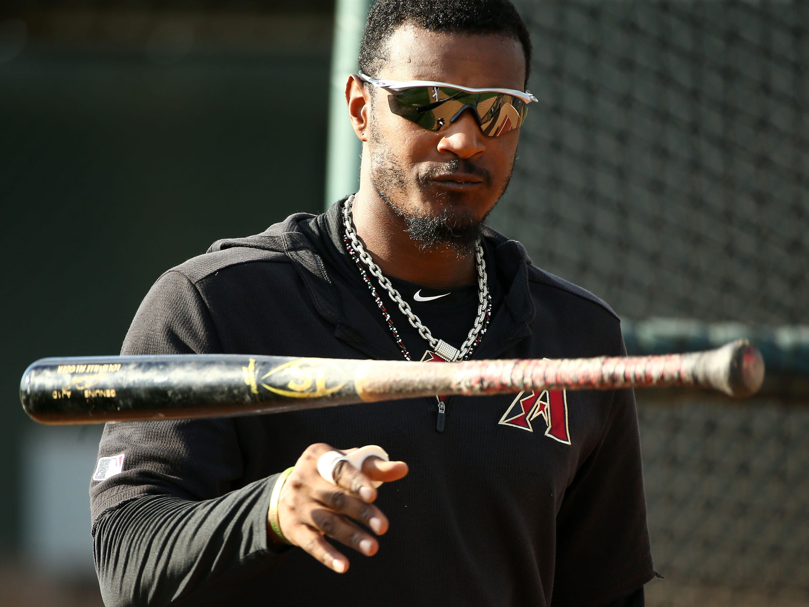 Arizona Diamondbacks outfielder Adam Jones flips his bat during spring training work-outs on Mar. 19, 2019 at Salt River Fields in Scottsdale, Ariz.