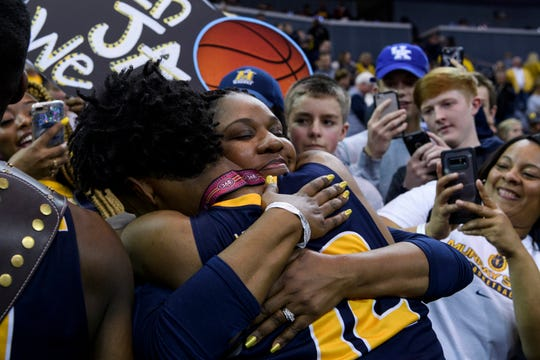 Murray State's Ja Morant (12) and his mother, Jamie Morant, embrace around a big crowd celebrating after the team's win over Belmont in an NCAA college basketball game for the Ohio Valley Conference men's tournament championship in Evansville, Ind., Saturday, March 9, 2019. (Sam Owens/Evansville Courier & Press via AP)