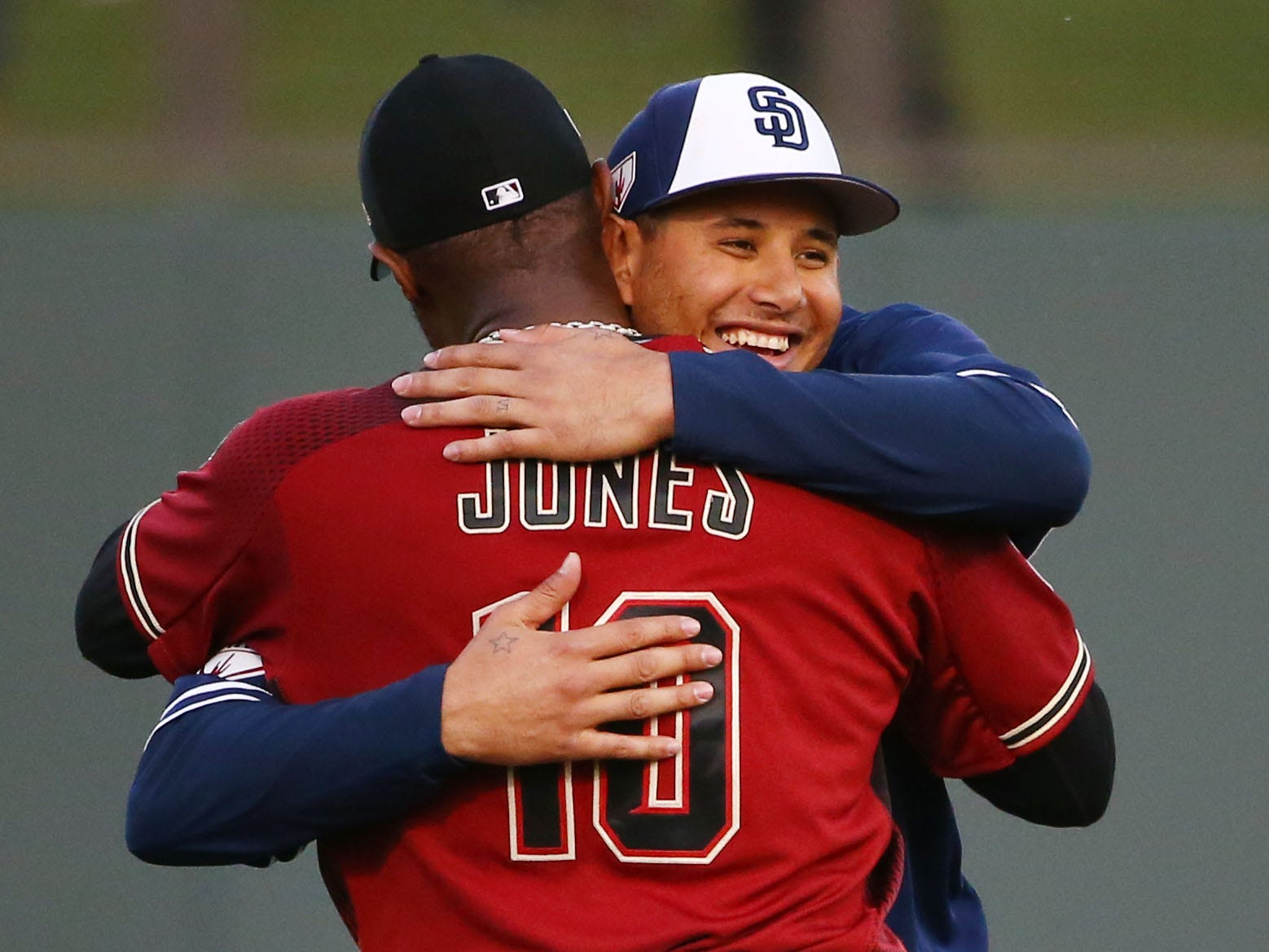 Arizona Diamondbacks Adam Jones (10) hugs San Diego Padres Manny Machado during a spring training game on Mar. 19, 2019 at Salt River Fields in Scottsdale, Ariz.