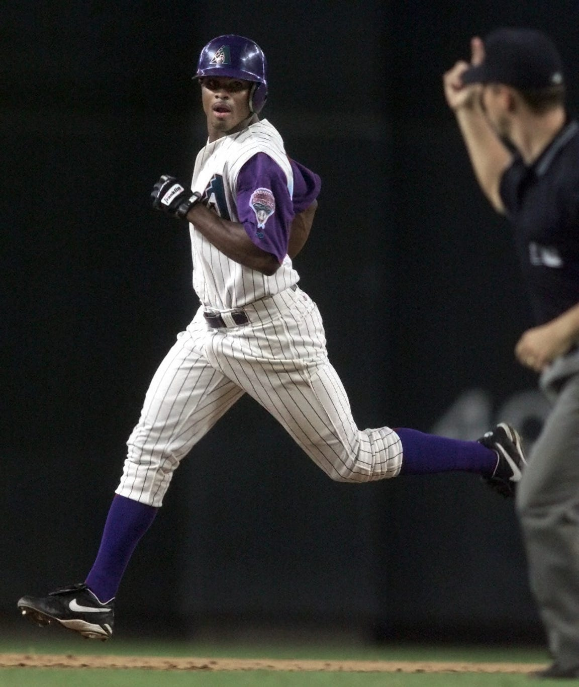 Arizona Diamondbacks' Junior Spivey rounds second base as the umpire signals a home run in a 2001 game against the Mets.