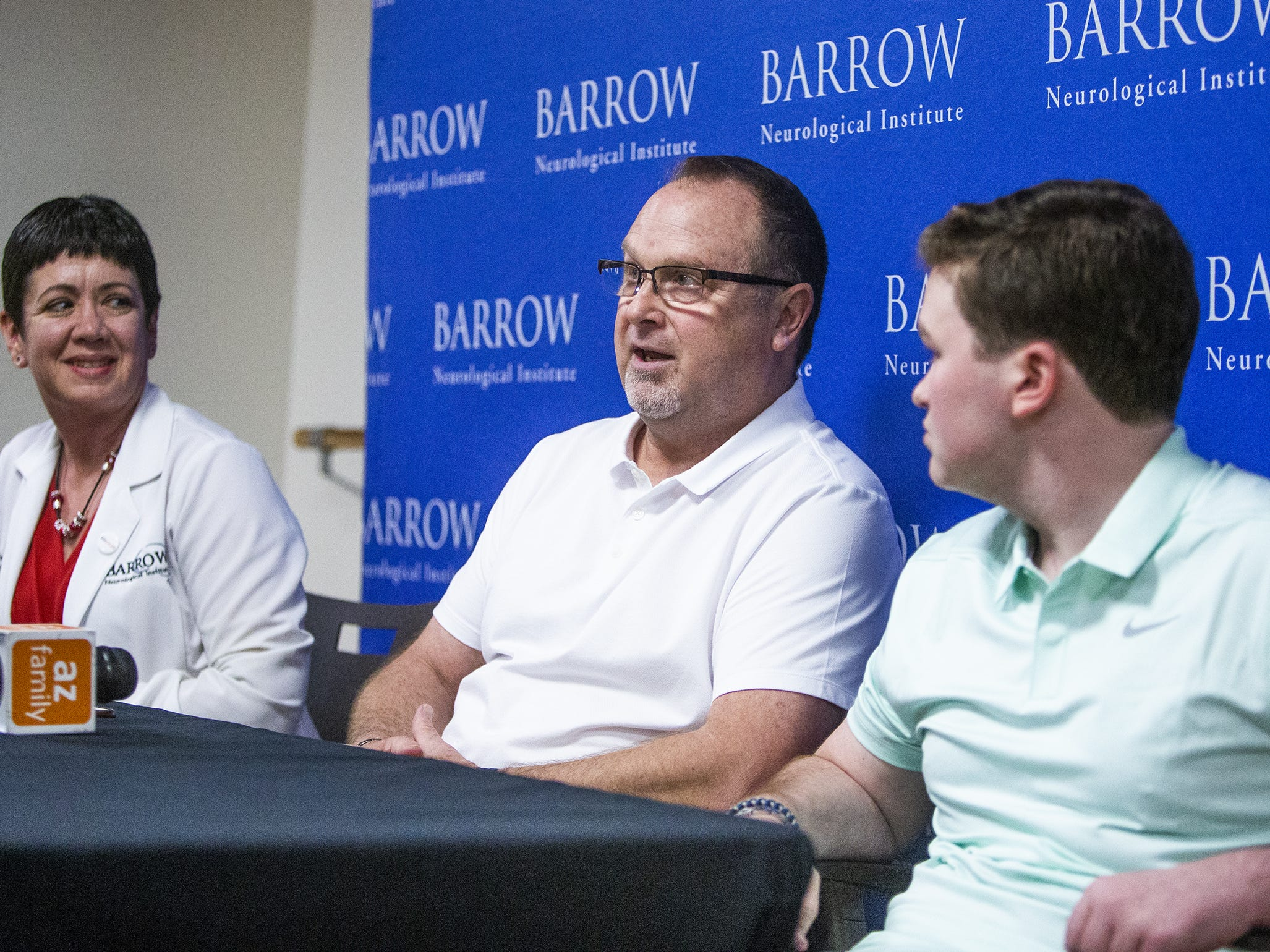 Brody Burnell, 20, right, survived a horrific airplane crash in 2017 and has made a miraculous recovery from multiple injuries, including traumatic brain injury.  Burnell and his doctor, Christina Kwasnica, M.D., left, and his father, Steve, middle, meet the press at Barrow Neurological Institute, Tuesday, March 19, 2019.
