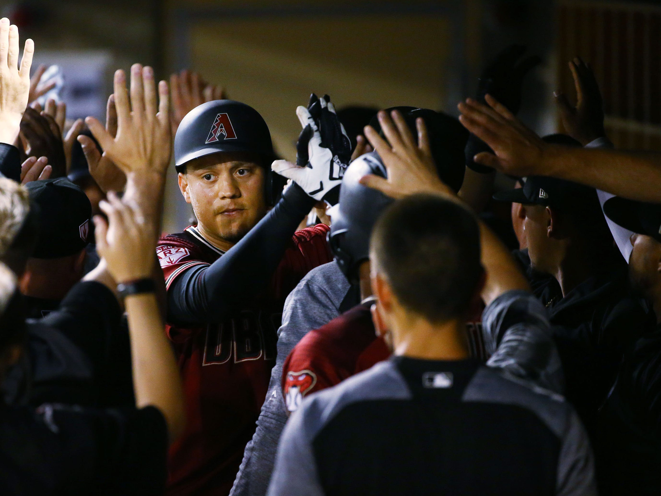 Arizona Diamondbacks Wilmer Flores (41) receives high-fives after hitting a RBI-sacrifice fly ball scoring David Peralta against the San Diego Padres in the first inning during a spring training game on Mar. 19, 2019 at Salt River Fields in Scottsdale, Ariz.