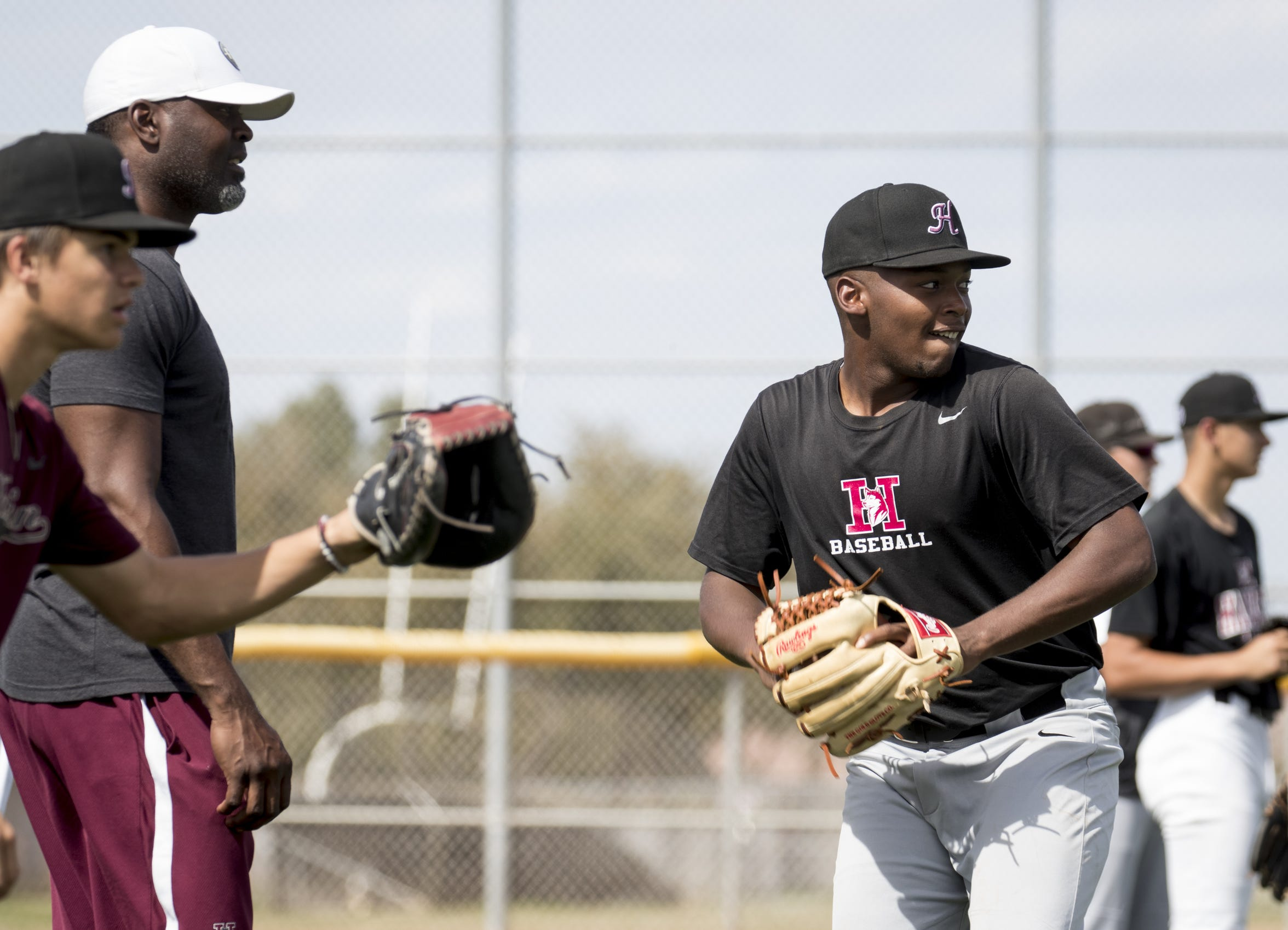 Jamie Brewington (second from left) works with Tally Wright (right front) during baseball practice, March 6, 2019, at Hamilton High School.