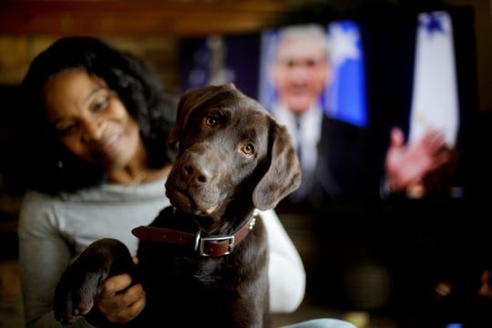 """Alicia Barnett se sienta junto a su mascota, un perro labrador color chocolate al cual bautizó con el nombre de """"Mueller""""."""