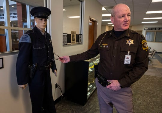 St. Clair County Sheriff Tim Donnellon discusses a uniform worn by the department Tuesday, March 19, 2019 in an exhibit created inside the St. Clair County Sheriff's Office. The department wore the blue uniforms until they switched to brown uniforms in the 1960's.