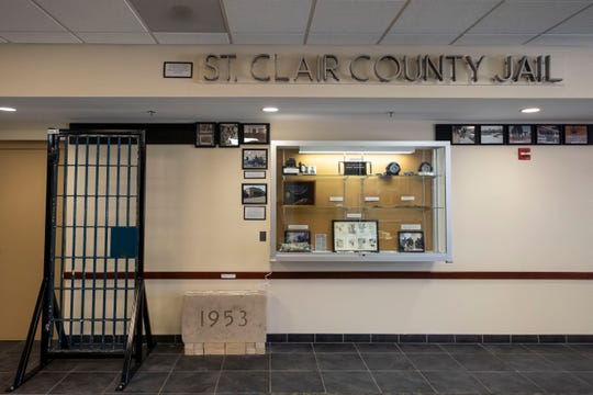 Lettering from the former Bard Street jail hangs above a cell door and a display case filled with historic items and photographs hanging inside the St. Clair County Sheriff's Office as part of an exhibit created to display the department's history.