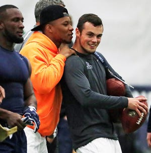 Former Penn State running back, now with the New York Giants, Saquon Barkley, center, hugs Penn State quarterback Trace McSorley, right, after his workout during Penn State's Pro Day in State College, Pa., Tuesday, March 19, 2019. (AP Photo/Gene J. Puskar)