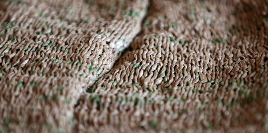 A close up view at the woman's suit made of only Wegman's  plastic shopping bags, gives a look of a knitted woolen sweater.