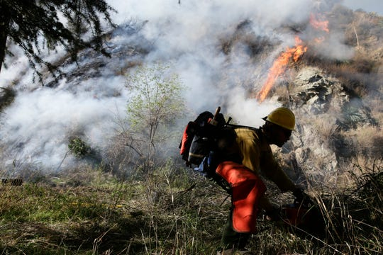 In this Jan. 17, 2014, file photo, a firefighter clears brush as firefighters continue to battle the Colby Fire near Azusa, Calif. California is calling in the National Guard for the first time to help protect communities from wildfires like the one that destroyed much of the city of Paradise last fall. The state is pulling the troops away from President Donald Trump's border protection efforts and devoting them to fire protection, another area where the president has been critical of California officials.