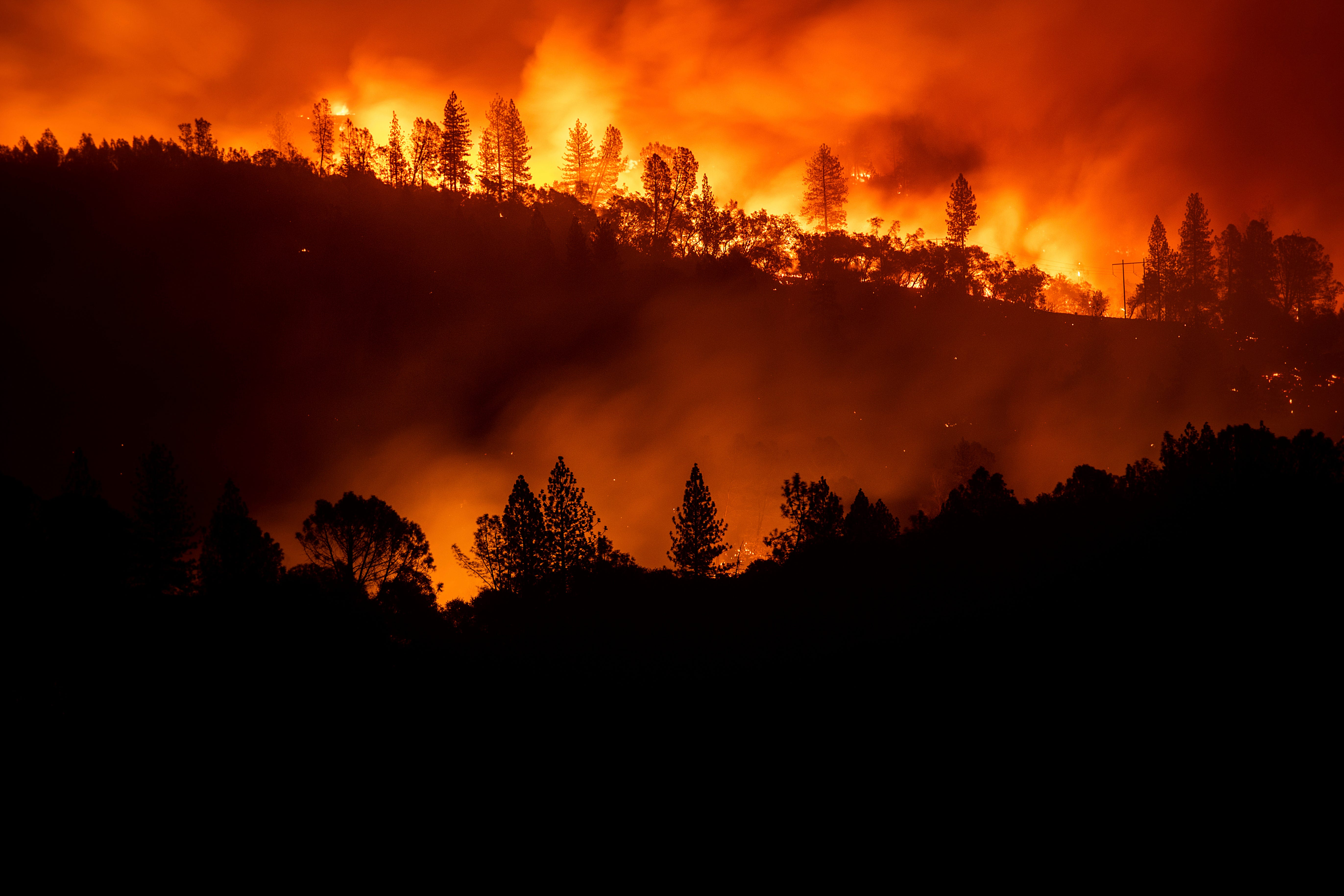 In this Nov. 10, 2018, file photo, the Camp Fire burns along a ridgetop near Big Bend, Calif. California is calling in the National Guard for the first time to help protect communities from wildfires like the one that destroyed much of the city of Paradise last fall. Starting in April 2019, 110 California National Guard troops will receive 11 days of training in using shovels, rakes and chain saws to thin trees and brush.