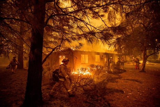 In this Nov. 9, 2018, file photo firefighters work to keep flames from spreading through the Shadowbrook apartment complex as a wildfire burns through Paradise, Calif. California is calling in the National Guard for the first time to help protect communities from wildfires like the one that destroyed much of the city of Paradise last fall. Starting in April 2019, 110 California National Guard troops will receive 11 days of training in using shovels, rakes and chain saws to thin trees and brush.
