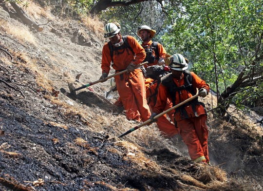 In this June 12, 2018, file photo, firefighters clear burned and unburned brush from a hillside above Portola Drive after a wildfire broke out in the Benedict Canyon area of Los Angeles. California is calling in the National Guard for the first time to help protect communities from wildfires like the one that destroyed much of the city of Paradise last fall. Starting in April 2019, 110 California National Guard troops will receive 11 days of training in using shovels, rakes and chain saws to thin trees and brush.