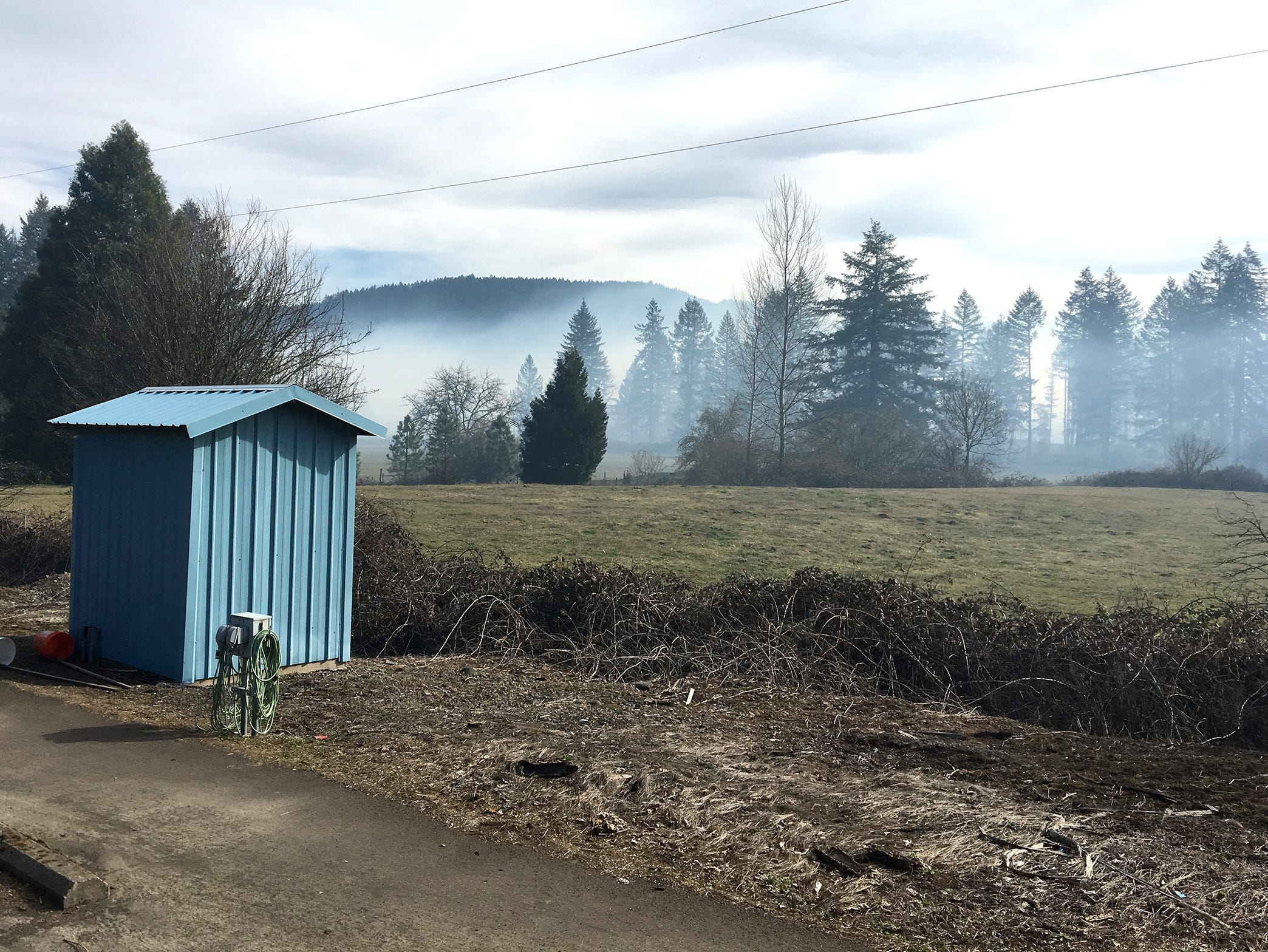 Smoke from a grass fire drifts over the North Santiam River near Lyons. The fire was first reported Tuesday afternoon in the North Santiam State Recreation Area.