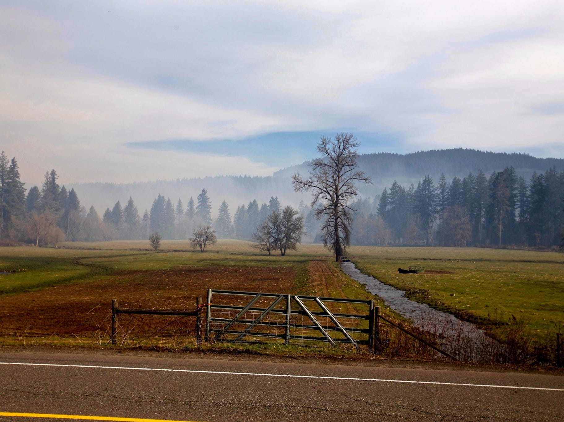 Smoke lingers near Lyons as a wildfire burns in North Santiam State Recreation Area Wednesday, March 20, 2019.