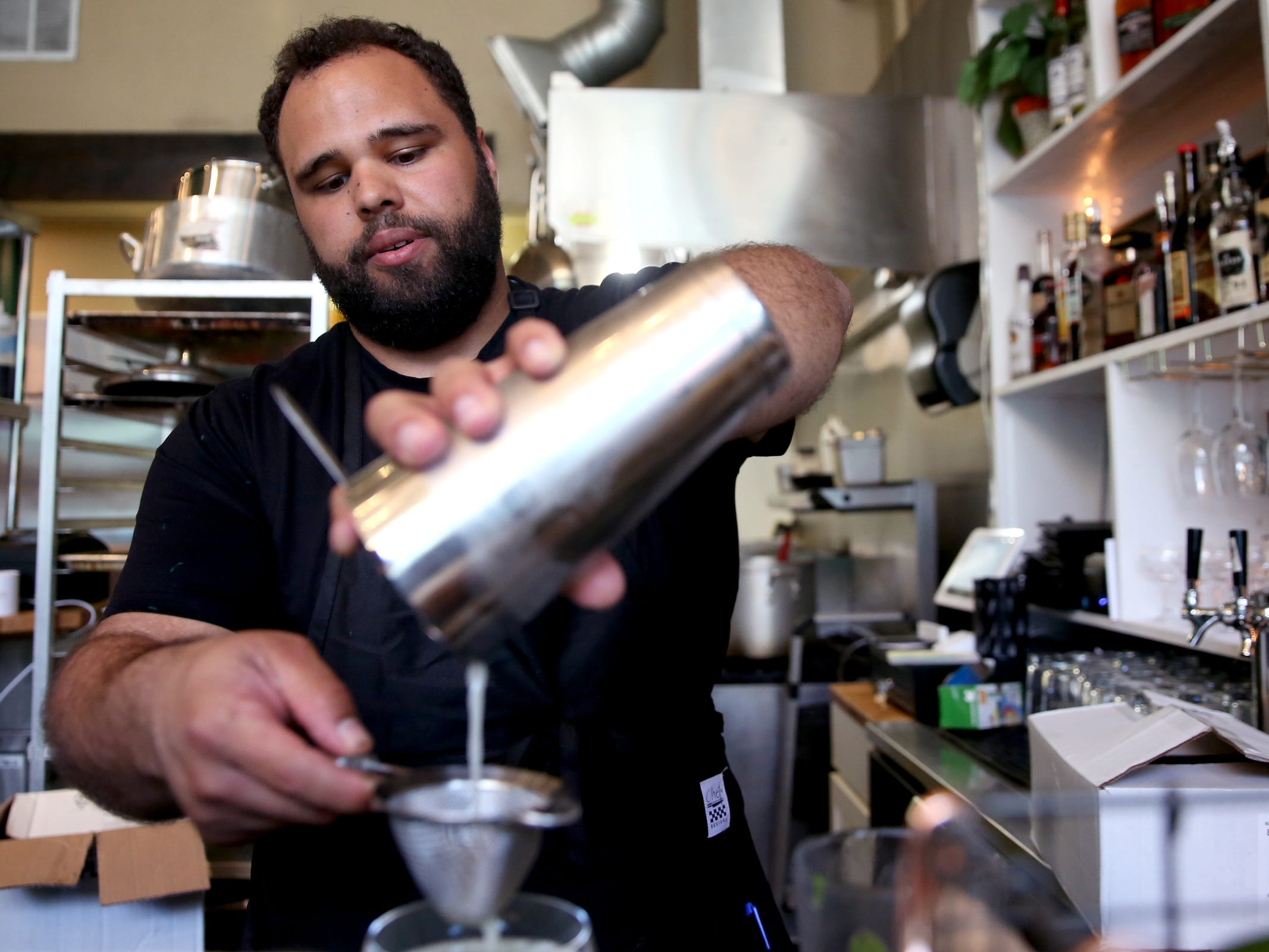 Jonathan Jones, the owner of Epilogue Kitchen & Cocktails makes a Rumspringa cocktail with cream of coconut, coconut rum, light rum, gin and mint in Salem on March 20, 2019. The restaurant opens in downtown Salem on Friday.