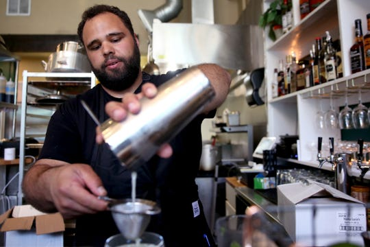 Jonathan Jones, the owner of Epilogue Kitchen & Cocktails makes a Rumspringa cocktail with cream of coconut, coconut rum, light rum, gin and mint in Salem on March 20, 2019. Though Epilogue's service remains modified due to COVID-19, the restaurant is offering no-contact takeout.
