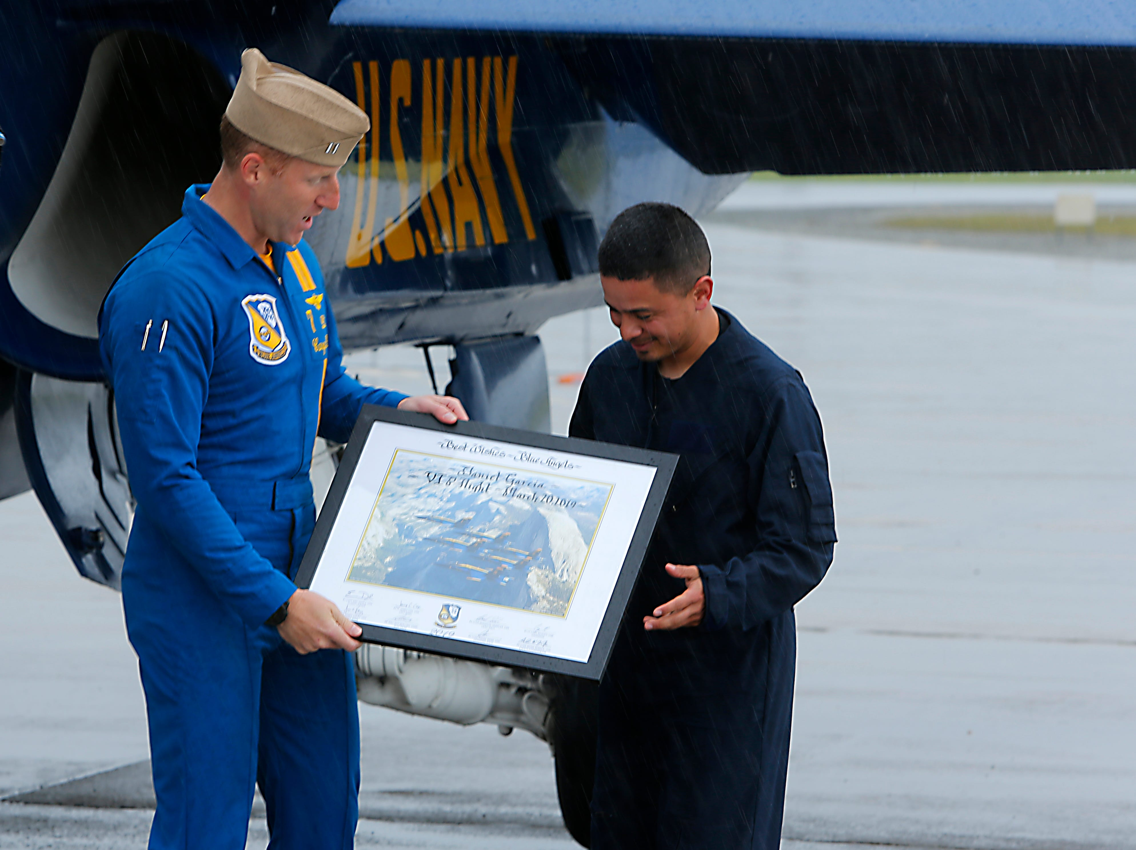 Lt. Cary Rickoff gives Salinas police officer Daniel Garcia a personalized and autographed photo of the Blue Angels performing.