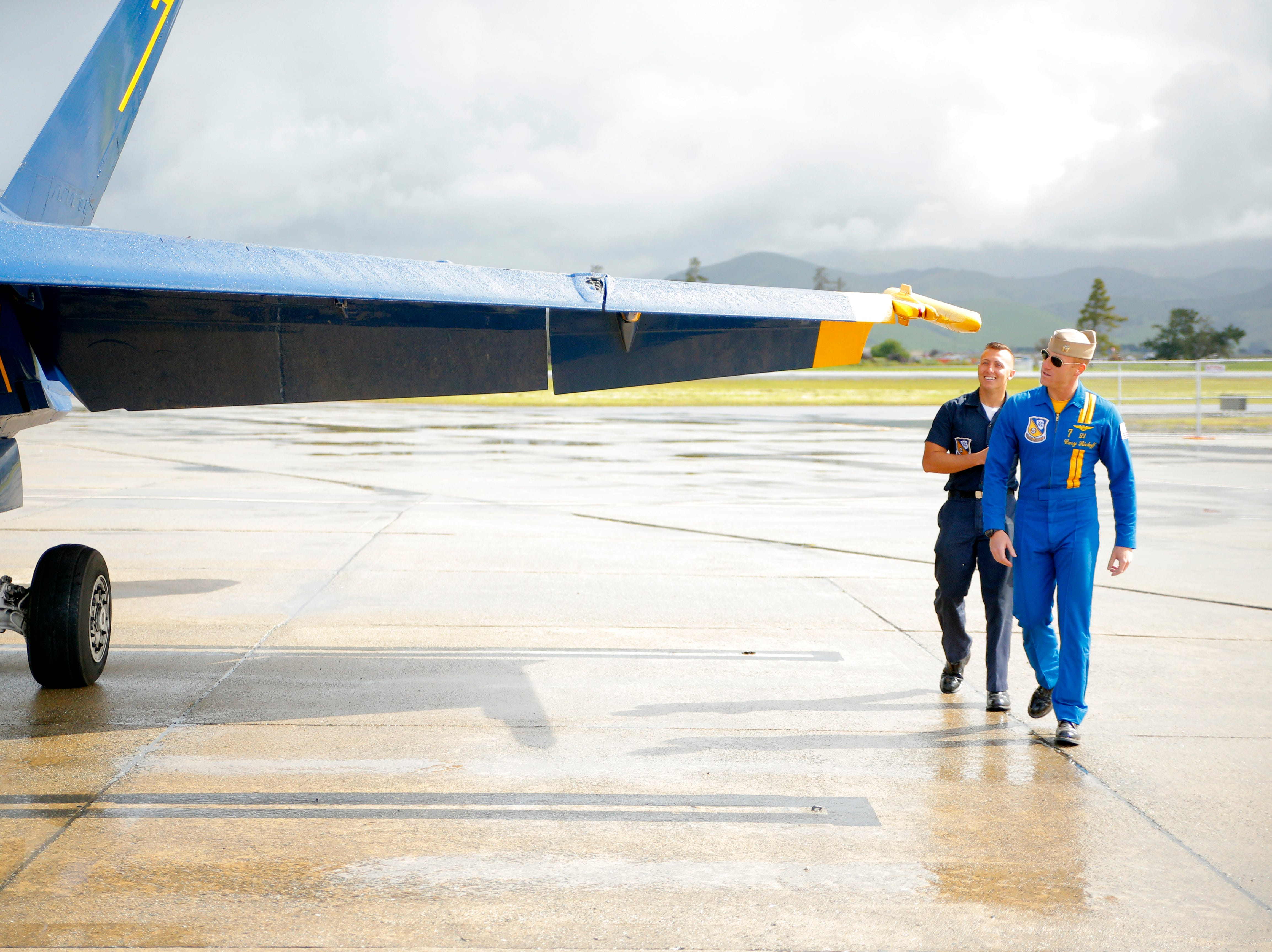 (From left:) U.S. Navy Petty Officer Kyle Wood and Lt. Cary Rickoff approach a jet fighter March 20, 2019. Rickoff piloted the jet to give Daniel Garcia ride before the California International Airshow Salinas.