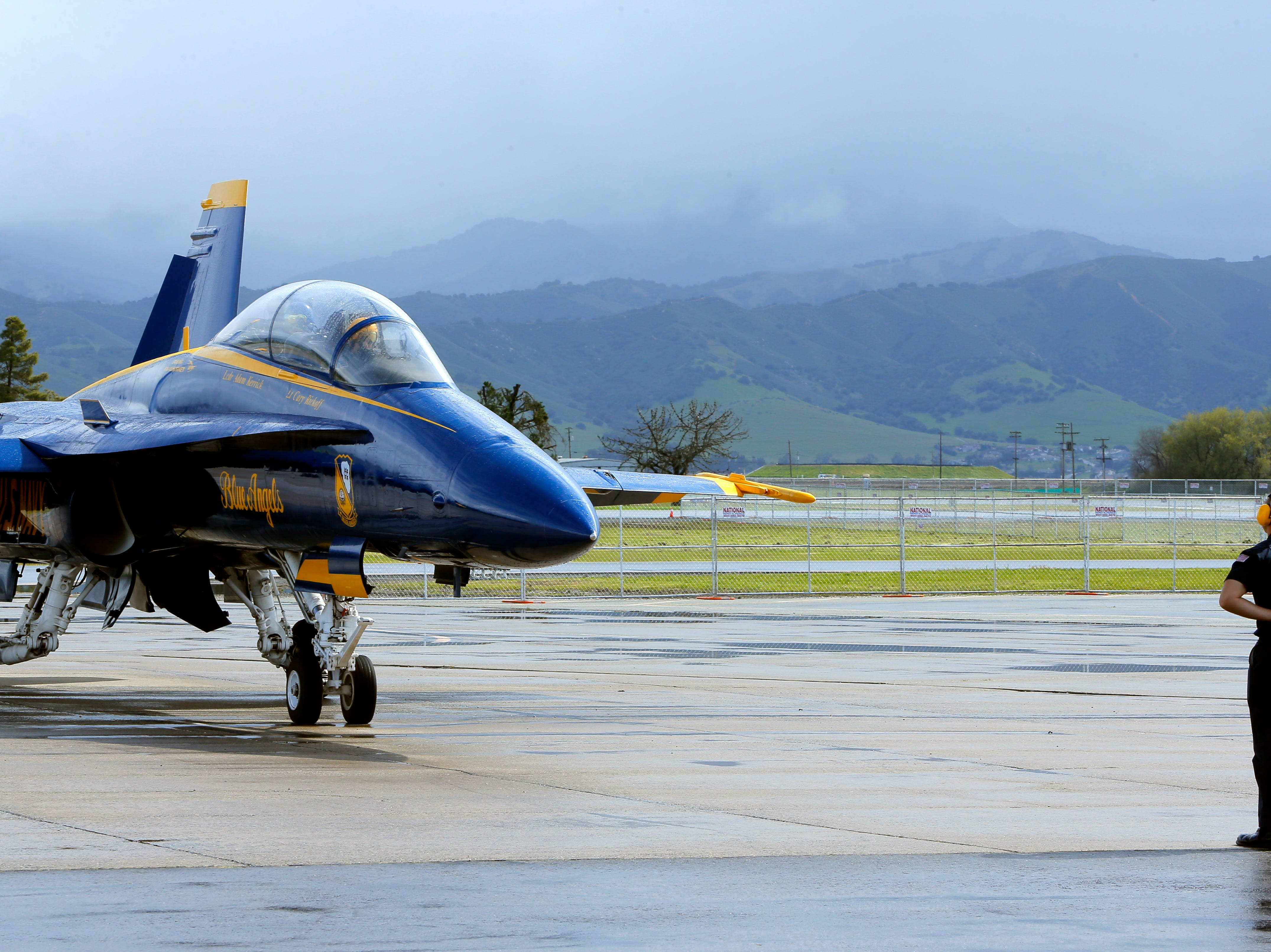 U.S. Navy Petty Officer Kyle Wood prepares to guide a Blue Angels jet fighter, which has Salinas police officer Daniel Garcia March 20, 2019. Garcia was selected to ride with the Blue Angels, who are performing in the California International Airshow Salinas.
