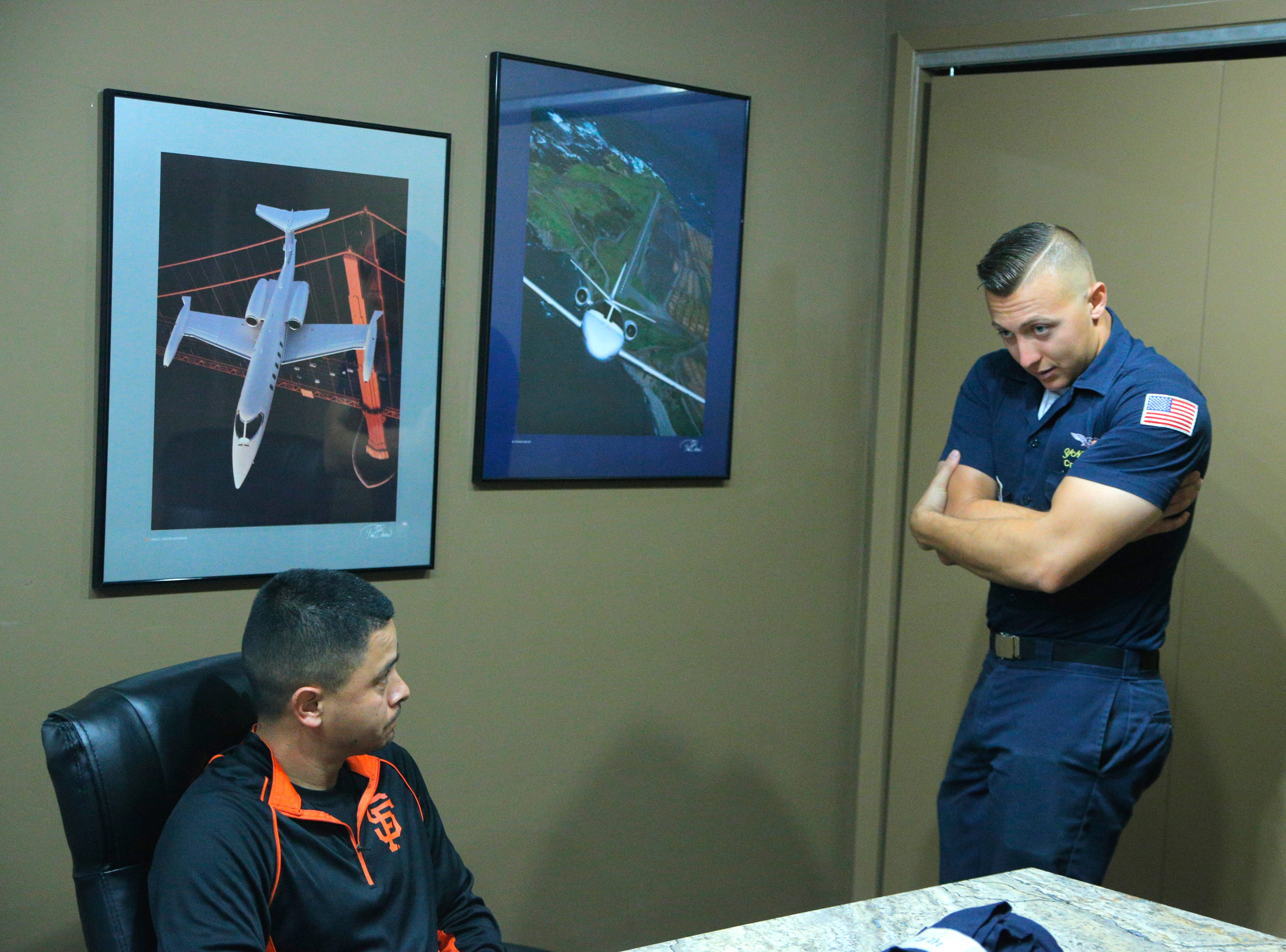 Salinas police officer Daniel Garcia (left) looks on as U.S. Navy Petty Officer Kyle Wood demonstrates the posture for an emergency ejection Wednesday at the California International Airshow Salinas.