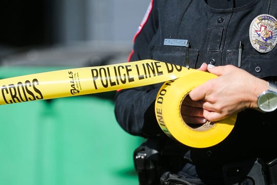 Police officer puts up tape at a scene.