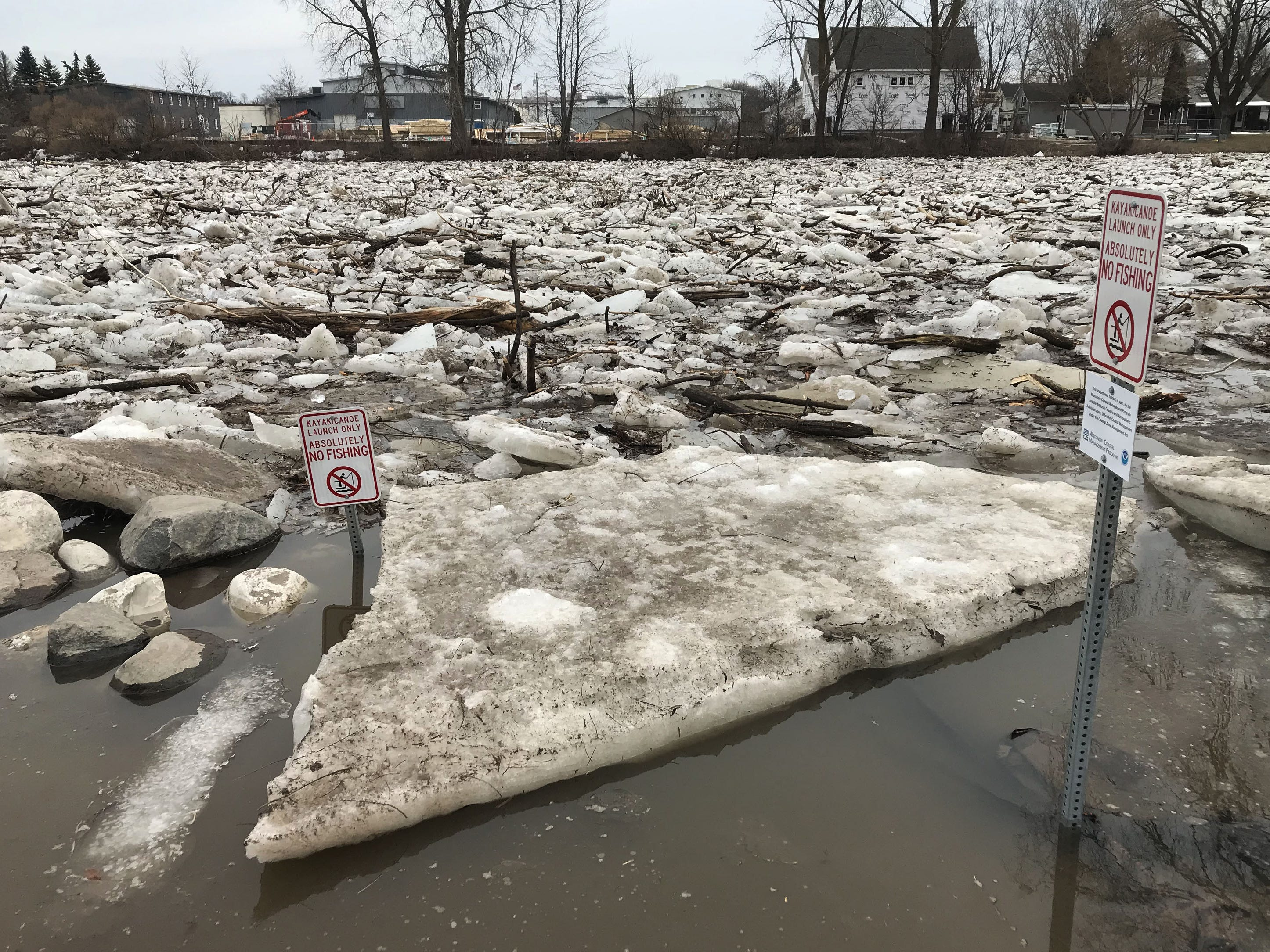 A big slab of ice parks next to a kayak/canoe signs at Kiwanis Park, Wednesday, March 20, 2019, in Sheboygan, Wis.