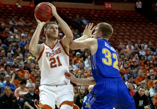 Texas forward Dylan Osetkowski (21) shoots over South Dakota State forward Matt Dentlinger (32) during a first round game of the NCAA college basketball National Invitation Tournament in Austin, Texas, Tuesday, March 19, 2019.