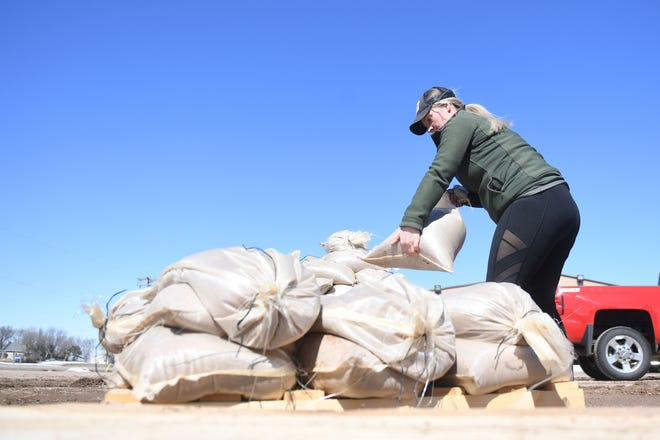Sandy Peckenpaugh stacks sandbags at a city shop Wednesday, March 20, in Dell Rapids. The 24 hour public sandbagging location at 24680 475th Ave. provided sandbags, shovels, and sand. Residents can stop by and fill sandbags themselves to prepare for flooding over the weekend.