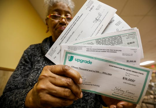 Patricia Reynolds shows some of the checks that she has been sent from payday loan companies following a press conference at Pitts Chapel United Methodist Church on Wednesday, March 20, 2019.