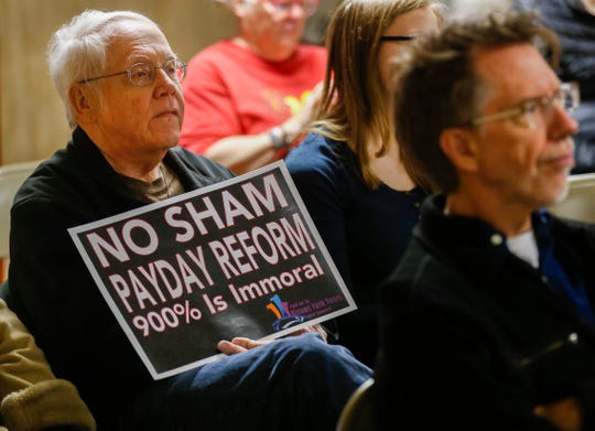 A member of the audience holds up a sign against payday lenders during a press conference at Pitts Chapel United Methodist Church on Wednesday, March 20, 2019.