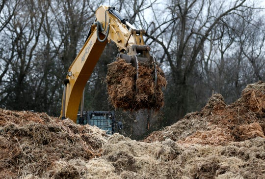 A piece of construction equipment moves part of a freshly mulched tree to another pile along East Sunshine Street, near Luster Avenue, where Hy-Vee has said it plans to build a new grocery store.