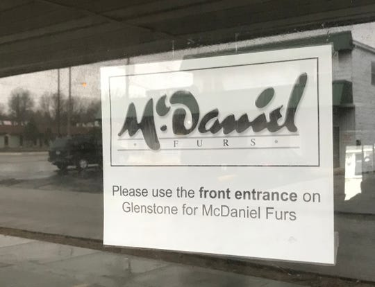 "The sign says ""use the front entrance,"" but you would have to drive over the curb to access the parking spaces along East Lombard Street. Is McDaniel Furs at 901 St. Glenstone Ave. open or closed?"
