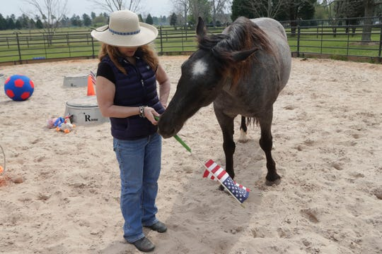 Teresa Leigh hands her horse Rune Nevada an American flag to hold Tuesday, March 19, 2019.
