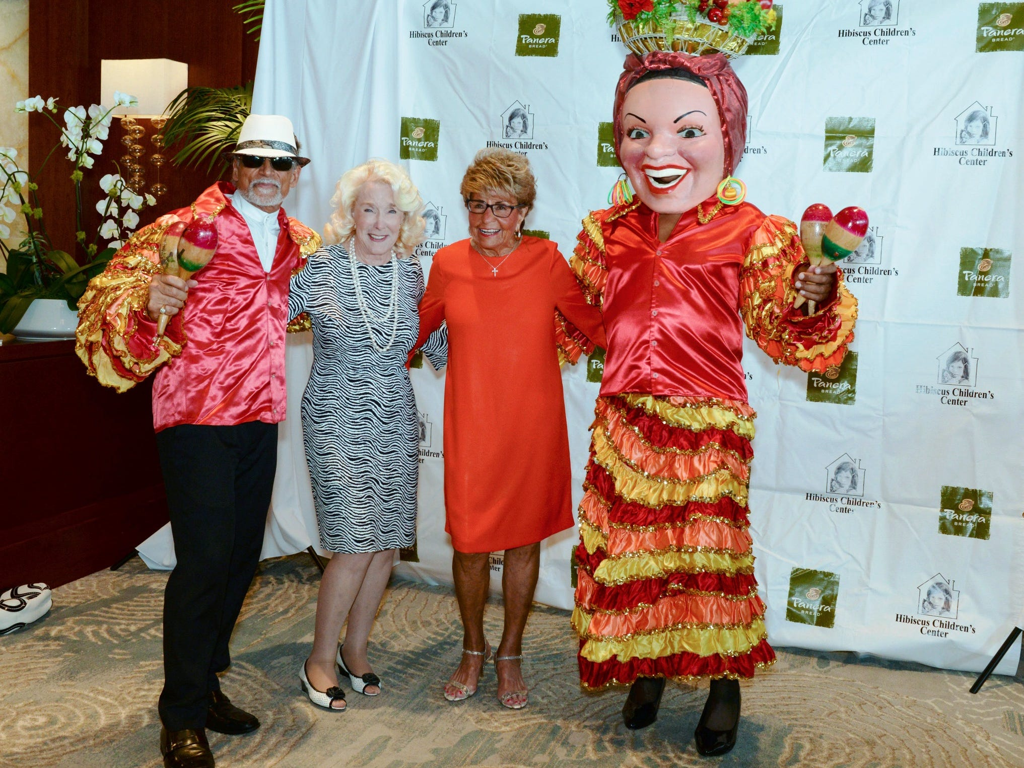 """""""The ChaCha Man"""" and """"Carmen Miranda"""" flank Pat Borg, second from left, and Luncheon Grand Benefactor Jo Covelli at the """"Hats off for Hibiscus"""" luncheon."""
