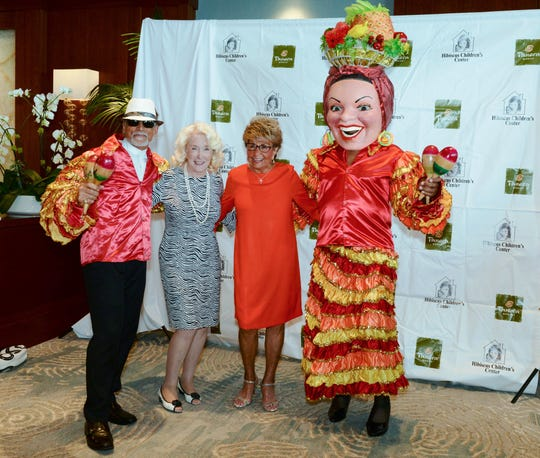 """The ChaCha Man"" and ""Carmen Miranda"" flank Pat Borg, second from left, and Luncheon Grand Benefactor Jo Covelli at the ""Hats off for Hibiscus"" luncheon."