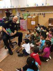 Fellsmere Chief of Police Keith Touchberry reads to children during Head Start Community Read Week in December 2016.