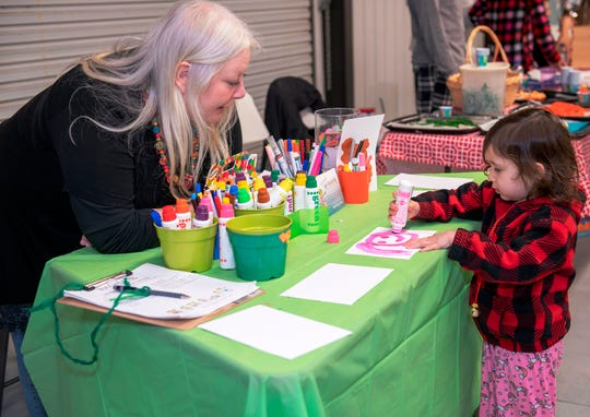 Kelly Bennis, left, of HulaFrog, talks to a child as she draws at the Pajama Jam to benefit The Language & Literacy Connection.